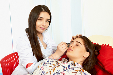 Master making correction of eyebrows in a beauty salon