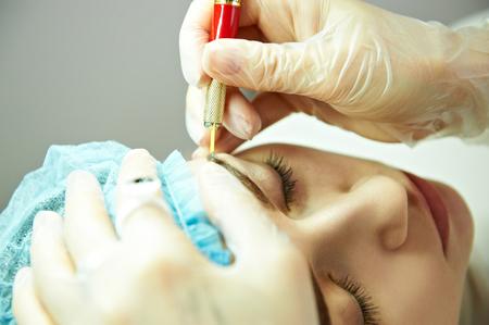 Cosmetician making permanent eyebrow make up. Eyebrow tattoo.