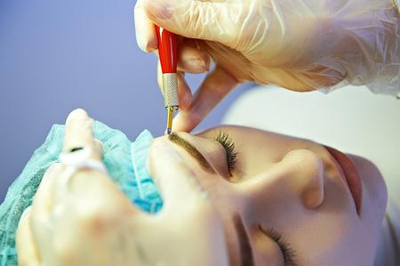 Cosmetician making permanent eyebrow make up for beautiful girl. Eyebrow tattoo.