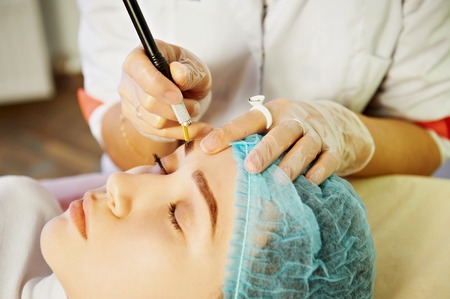 Cosmetician making permanent eyebrow make up for beautiful girl. Eyebrow tattoo. Close up.