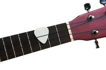fingerboard: White pick with ukulele fingerboard, isolated on white background Stock Photo