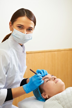Permanent make-up wizard makes eyebrow correction procedure. Stock Photo