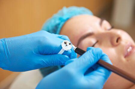 Permanente make-up wizard maakt wenkbrauw correctie procedure.