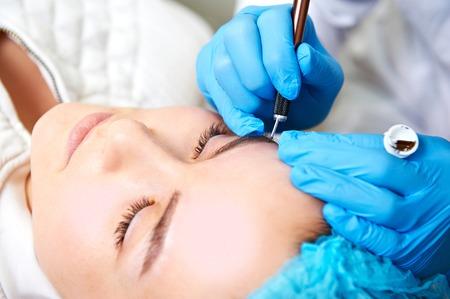 pinzas: asistente de maquillaje permanente hace procedimiento de corrección de cejas.