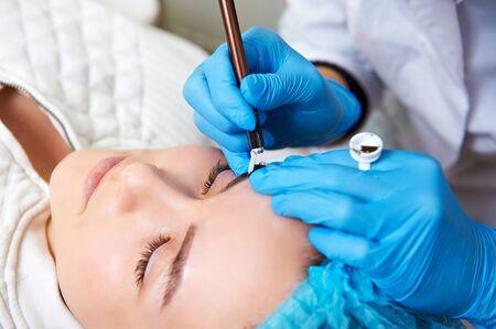 pinzas: Permanent make-up wizard makes eyebrow correction procedure. Foto de archivo