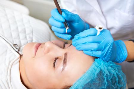 Permanent make-up wizard makes eyebrow correction procedure. Banco de Imagens