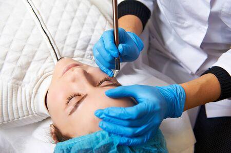 plucking: Permanent make-up wizard makes eyebrow correction procedure. Stock Photo