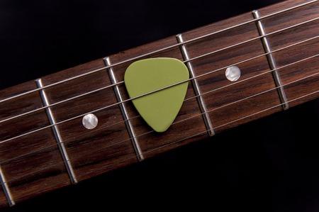 hardrock: Green guitar pick on the fingerboard Stock Photo