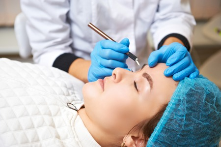 Permanent make-up wizard makes eyebrow correction procedure. Microblading