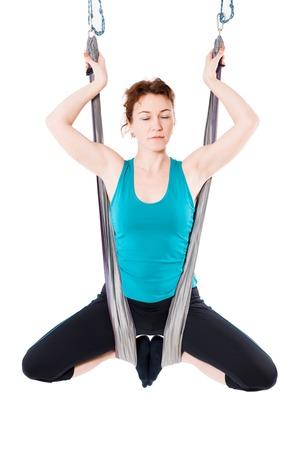 gravedad: Mujer joven practica yoga aéreo anti-gravedad con una hamaca