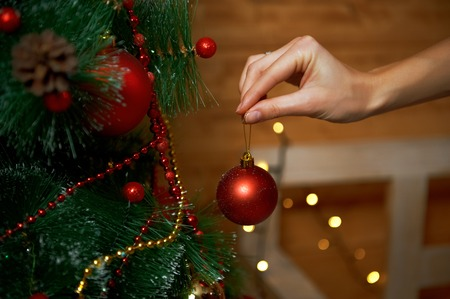 Girl hanging decorative toy ball on xmas tree