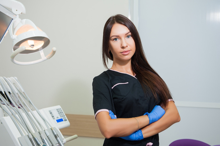 Happy young female dentist over medical office background Stock Photo