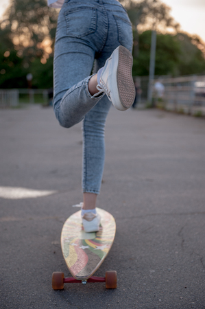 Street sports: A girl pushes off with her foot and rolls on a longboard.