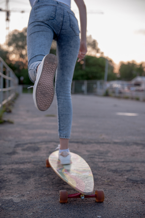 A girl pushes off with her foot and rolls on a longboard.