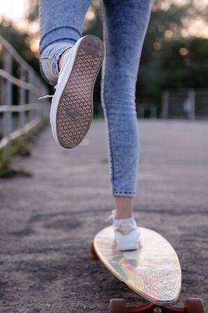 Girl with longboard wearing sneakers shoes in urban style