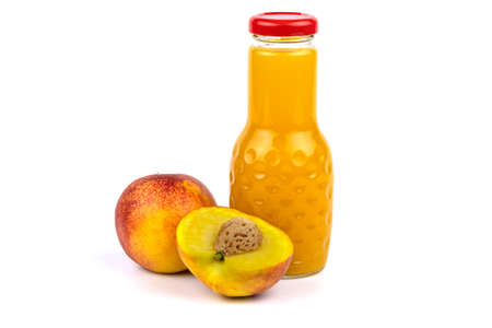A bottle of nectarine juice. Nearby are juicy, beautiful nectarines. Studio photo on a white background.