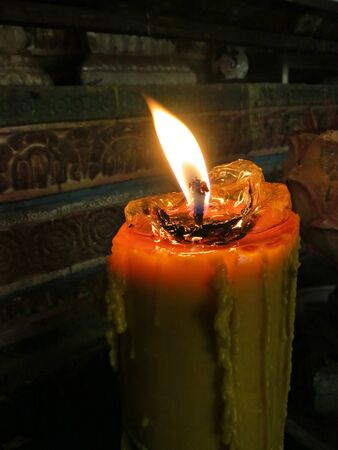 spellbinding: Large candle burning in a temple near the holy statue    Stock Photo