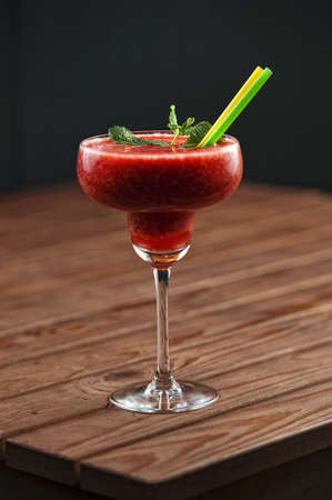 Strawberry margarita coctail with ice and meta decoration