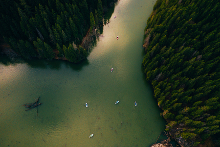 Lake ina pine tree forest with small boats seen from a drone