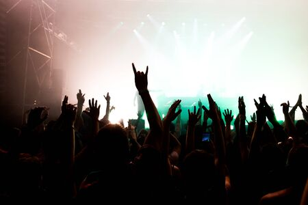 Stage lights and crowd of audience with hands raised at a music festival. Fans enjoying the party vibes.