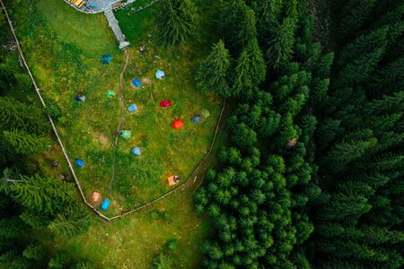 Camping site with tents seen from a drone in the dense woods.