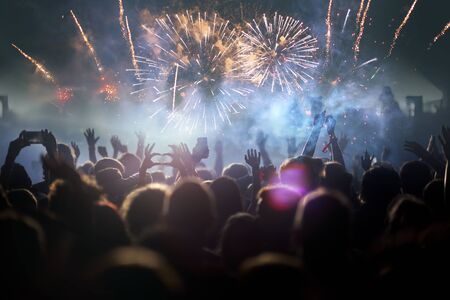 Stage lights and crowd of audience with hands raised at a music festival. Fans enjoying the party vibes. Banco de Imagens