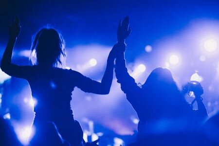 Stage lights and crowd of audience with hands raised at a music festival. Fans enjoying the party vibes. Stock Photo