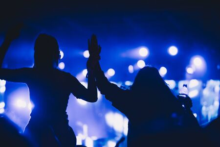 Stage lights and crowd of audience with hands raised at a music festival. Fans enjoying the party vibes. Foto de archivo