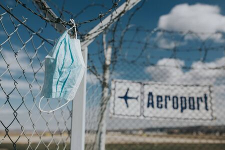 Surgical mask blown by the wind at the airport got stuck on the wired fence. Representative image for coronavirus outbreak and cancelled flights.