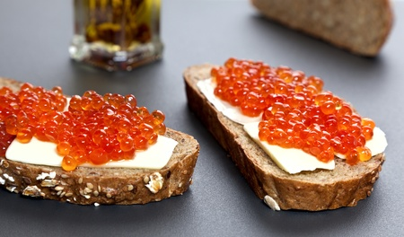 Two sandwiches with red caviar on the table