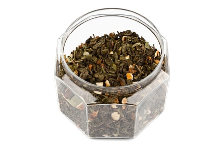 gunpowder tea: Faceted glass jar with a green fruit tea Stock Photo