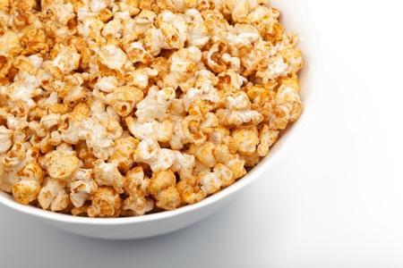 Full bowl of fresh popcorn on white background