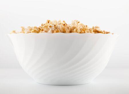 Big bowl of salty popcorn on light grey background