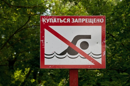 no swimming: Red sign prohibiting swimming in the lake in the woods