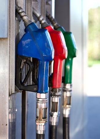 petrol pump: Three Colorful Pump Nozzles At The Gas Station Stock Photo