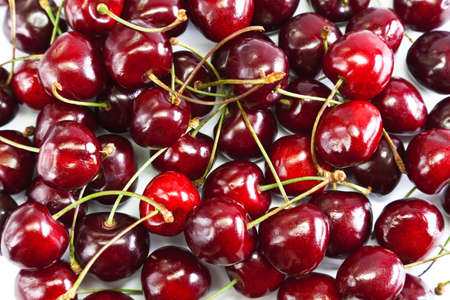Red Ripe Cherries Laid On White Table Stock Photo