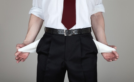 The businessman in a white shirt and black trousers shows his empty pockets