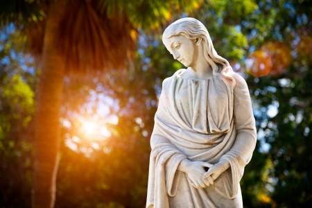 A young woman with folded hands looking down  Sculpture in the park Stock Photo