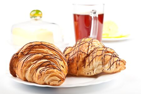 Two fresh croissants with chocolate on white plate