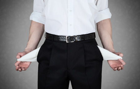 Businessman in white shirt shows empty pockets of his trousers Imagens