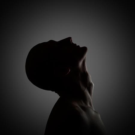 Creepy profile of the mysterious man. Low-key lighting photo