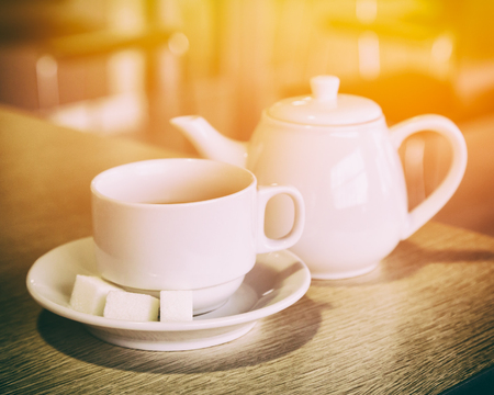 sugar cube: Cup of tea and teapot on the table it the cafe. Shallow depth of field Stock Photo