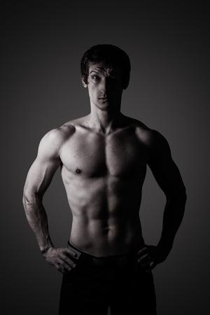 hombre desnudo: Retrato del estudio de un hombre joven deportiva en clave baja