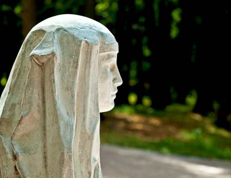 Stone profile of a beautiful young woman in the park in summer