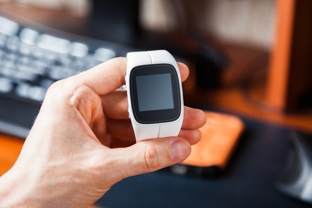 Hand holding a modern smart watch. Blank screen for placing your own information