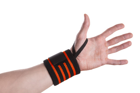 Calloused hand of a weightlifter with black and orange wrist wrap isolated on white background Stock Photo
