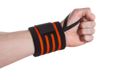carpal tunnel syndrome: Clenched hand of a weightlifter with black and orange wrist support bandage isolated on white background Stock Photo
