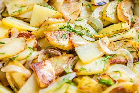 Delicious fried potatoes with onion and fresh dill closeup. Selective focus, very shallow depth of field