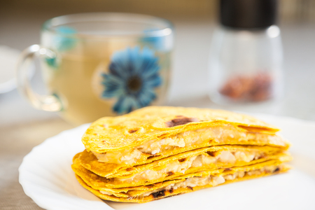 Delicious quesadillas with crispy corn tortillas on a white plate. A traditional Mexican meal. Beautiful bokeh, very shallow depth of field Stock Photo