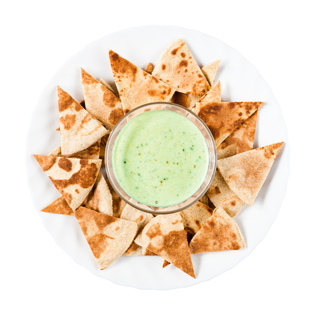 Delicious homemade nachos with green guacamole on a round white plate. Traditional Mexican food. Top view, isolated on white background